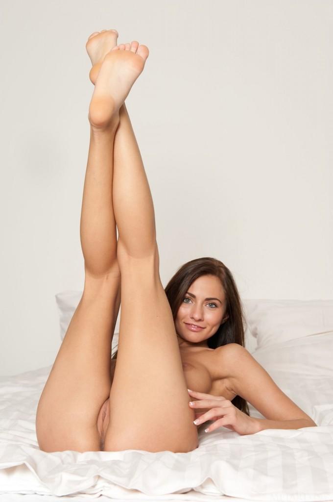 Wesoła brunetka pozuje na łóżku